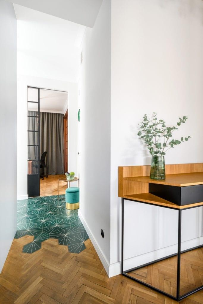 W+M Architektura i projekt biura na warszawskim Mokotowie - drewniana komoda stojąca pod ścianą