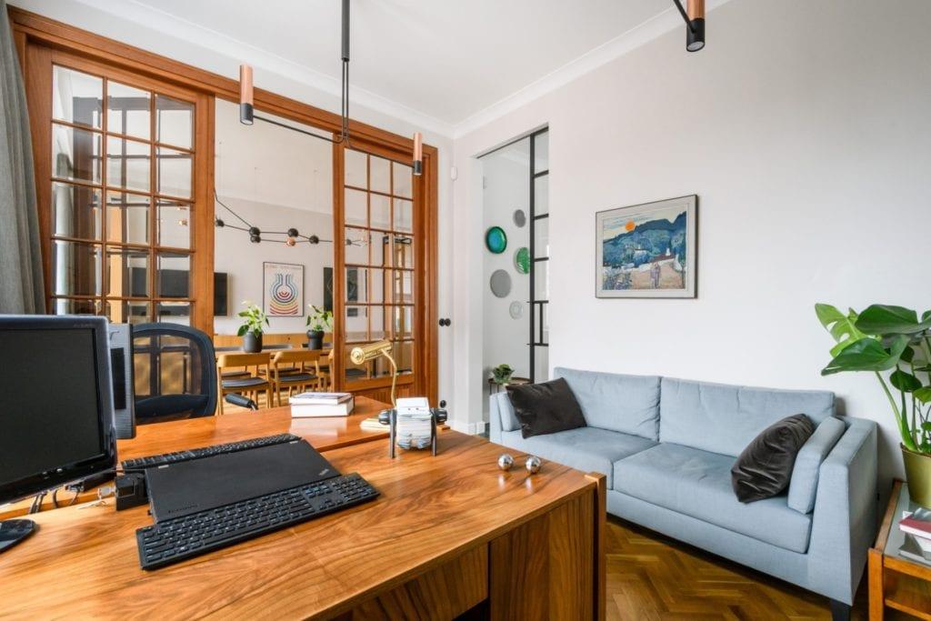 W+M Architektura i projekt biura na warszawskim Mokotowie - niebieska sofa stojąca w salonie