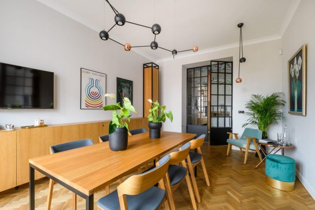 W+M Architektura i projekt biura na warszawskim Mokotowie - drewniany stół z kompletem krzeseł stojący w salonie
