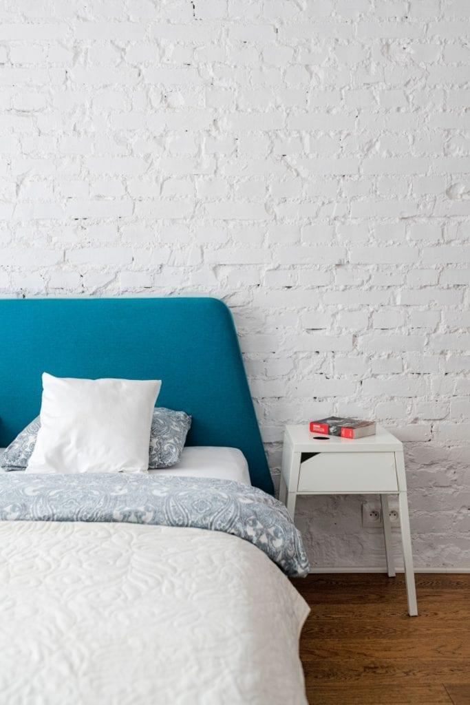 Decoroom i Stylowy mikroapartament w samym centrum Warszawy - minimalistyczna sypialnia z białą cegłą na ściana