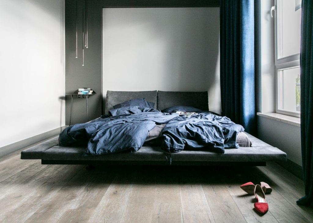 Joanna Zabłocka studio projekowania wnętrz - projekt poznańskiego apartamentu - duże szare łóżko z niebieską pościelą w ciemnej sypialni