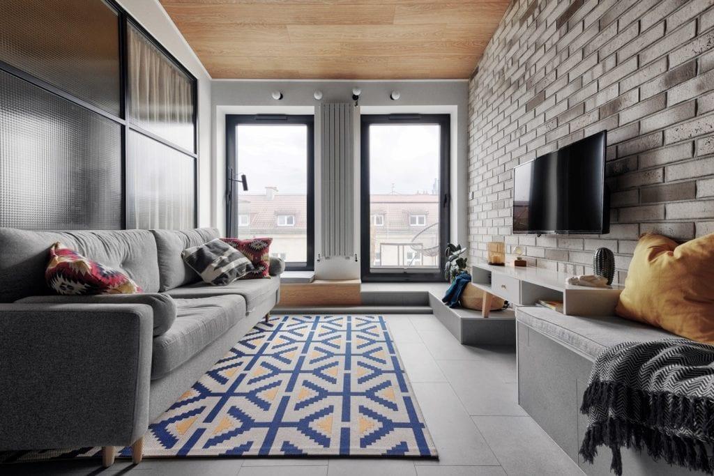 Krakowski apartament od pracowni bukaDesign - Klaudia Siudak - salon z jasną cegłą na ścianie