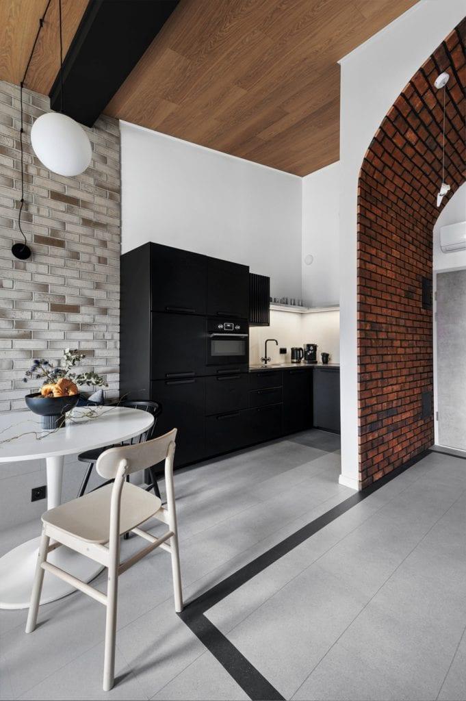 Krakowski apartament od pracowni bukaDesign - Klaudia Siudak - jasna i ciemna cegła na ścianie w kuchni