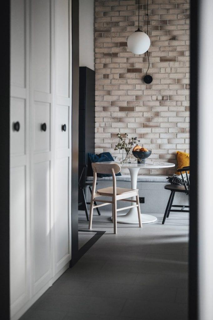 Krakowski apartament od pracowni bukaDesign - Klaudia Siudak - cegła na ścianie w jadalni