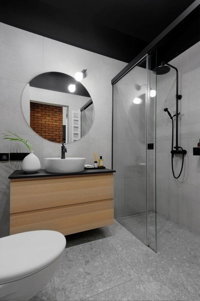 Krakowski apartament od pracowni bukaDesign - Klaudia Siudak - duże okrągłe lustro na ścianie w łazience, kabina prysznicowa, szafka łazienkowa w kolorze jasnego dębu