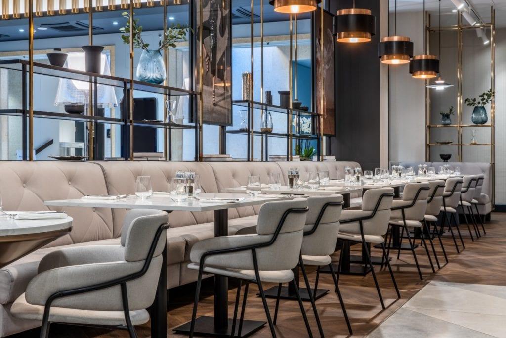 Radisson Blu w Pradze zaprojektowany przez polską pracownię Iliard Architecture & Project Management - szare krzesła w części restauracyjnej