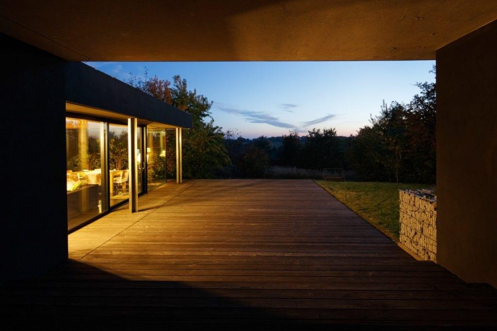 Dom z prześwitem - projekt, który architekt Robert Skitek z pracowni RS+ stworzył dla siebie oraz swoich najbliższych - Dom z prześwitem - projekt, który architekt Robert Skitek z pracowni RS+ stworzył dla siebie oraz swoich najbliższych - podświetlony taras