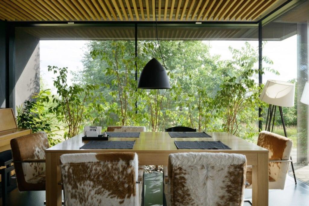Dom z prześwitem - projekt, który architekt Robert Skitek z pracowni RS+ stworzył dla siebie oraz swoich najbliższych - Dom z prześwitem - projekt, który architekt Robert Skitek z pracowni RS+ stworzył dla siebie oraz swoich najbliższych - stół z kompletem krzeseł