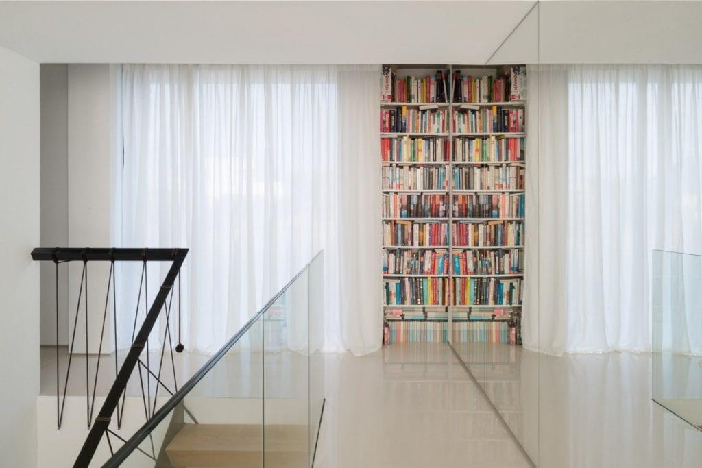 Dom z prześwitem - projekt, który architekt Robert Skitek z pracowni RS+ stworzył dla siebie oraz swoich najbliższych - Dom z prześwitem - projekt, który architekt Robert Skitek z pracowni RS+ stworzył dla siebie oraz swoich najbliższych - regał na książki na piętrze