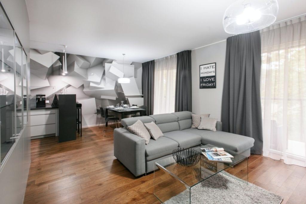 Dominik Ćwiek i funkcjonalny warszawski apartament - salon z szarą sofą