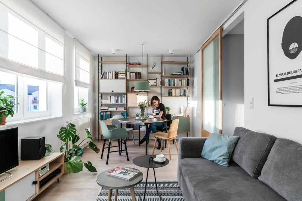 Projekt mieszkania w Gdańsku od pracowni Raca Architekci - salon z szarą sofą