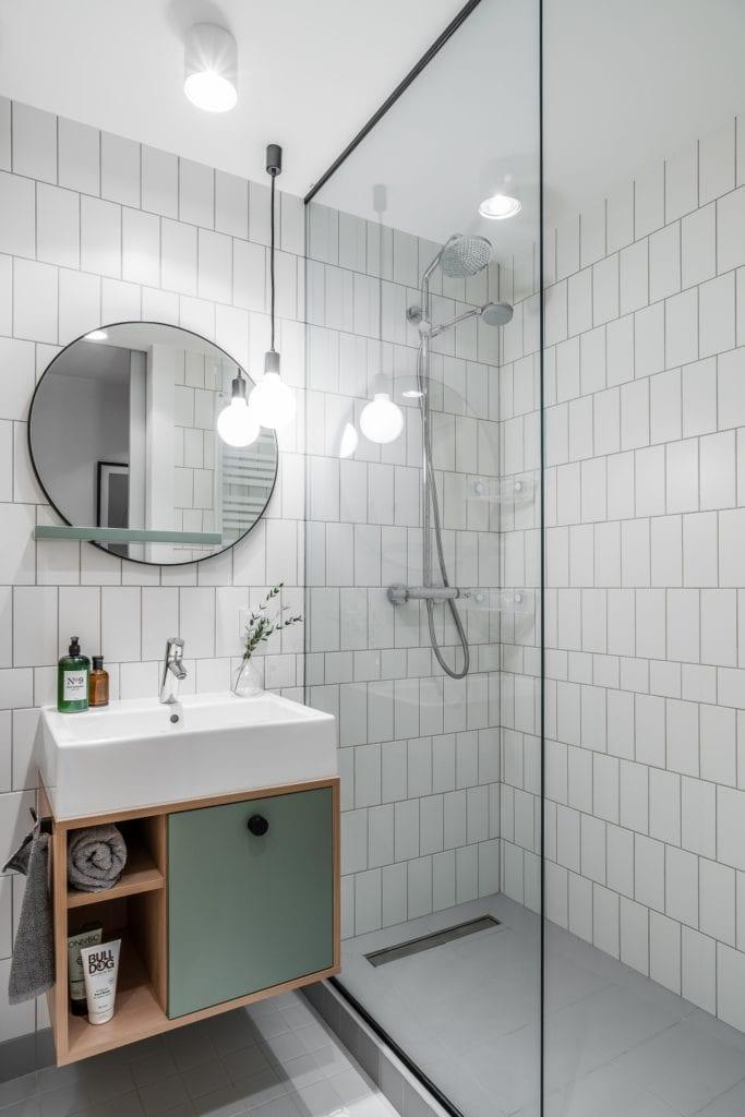 Projekt mieszkania w Gdańsku od pracowni Raca Architekci - okrągłe lustro na ścianie w łazience