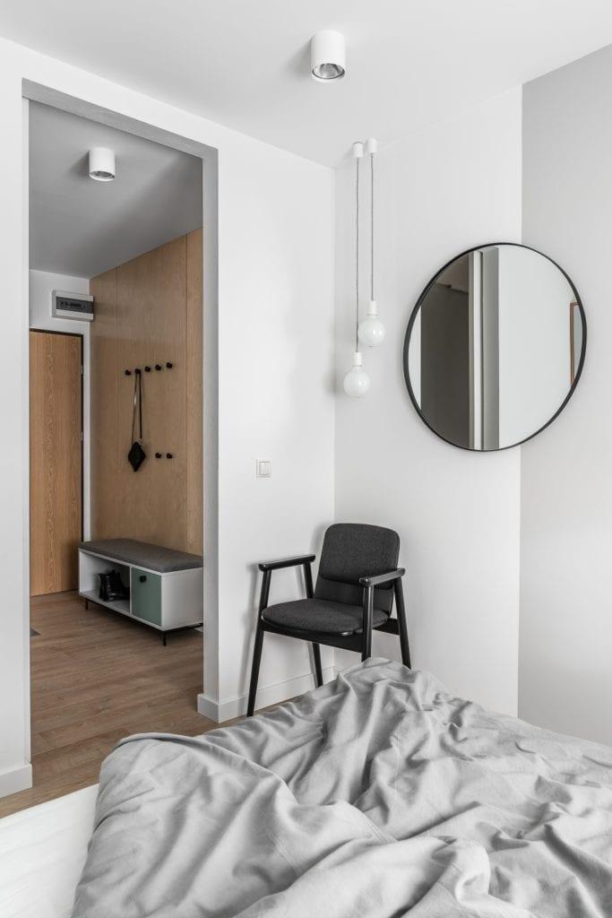 Projekt mieszkania w Gdańsku od pracowni Raca Architekci - okrągłe lustro na ścianie w sypialni