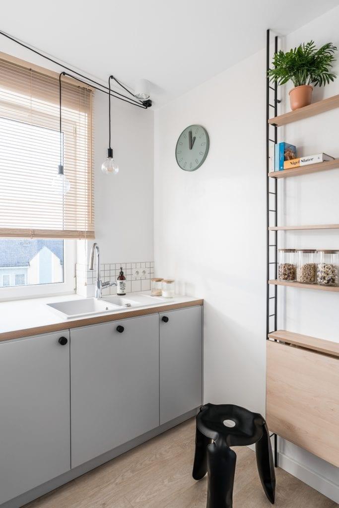 Projekt mieszkania w Gdańsku od pracowni Raca Architekci - szare fronty meblowe w kuchni