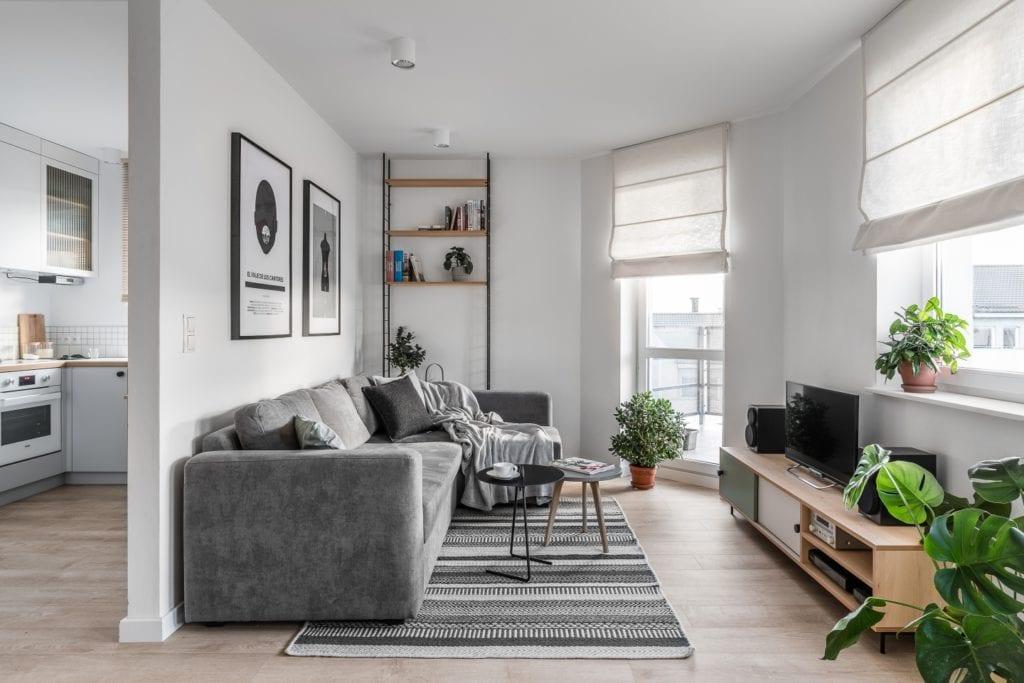 Projekt mieszkania w Gdańsku od pracowni Raca Architekci - szara sofa w salonie