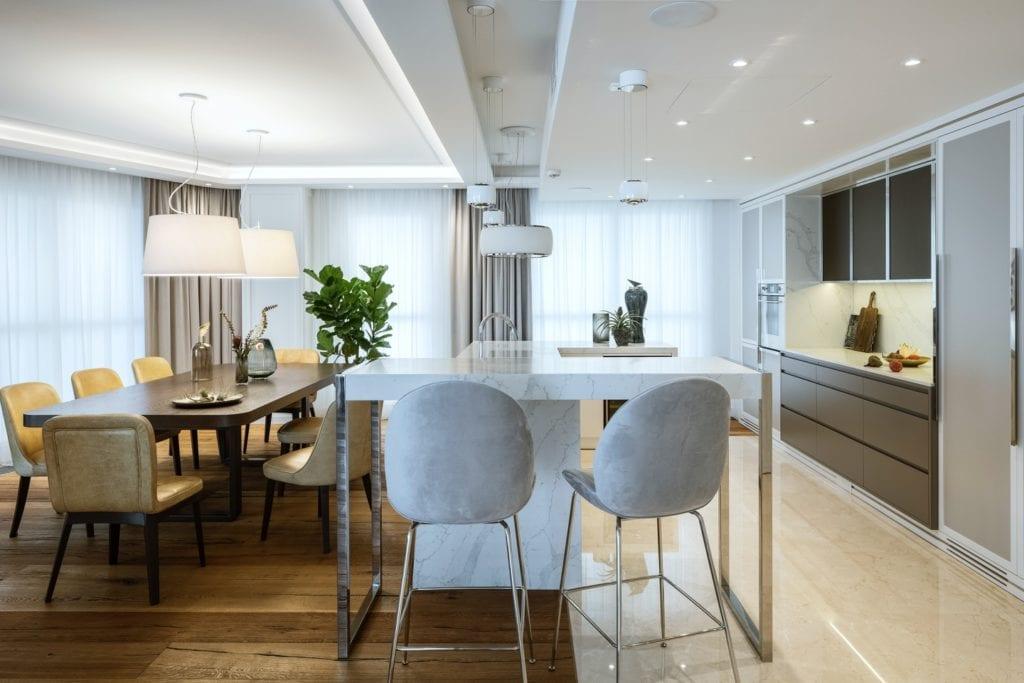 Warszawski apartament projektu pracowni HOLA Design - salon ze stołem i krzesłami