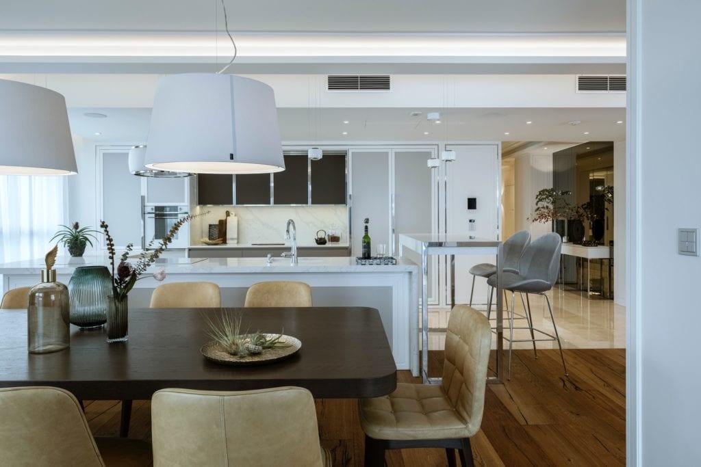 Warszawski apartament projektu pracowni HOLA Design - duży salon ze stołem i krzesłami