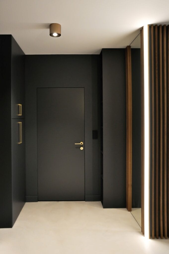 Czarne drzwi w ciemnym przedpokoju w projekcie studia MAUVE