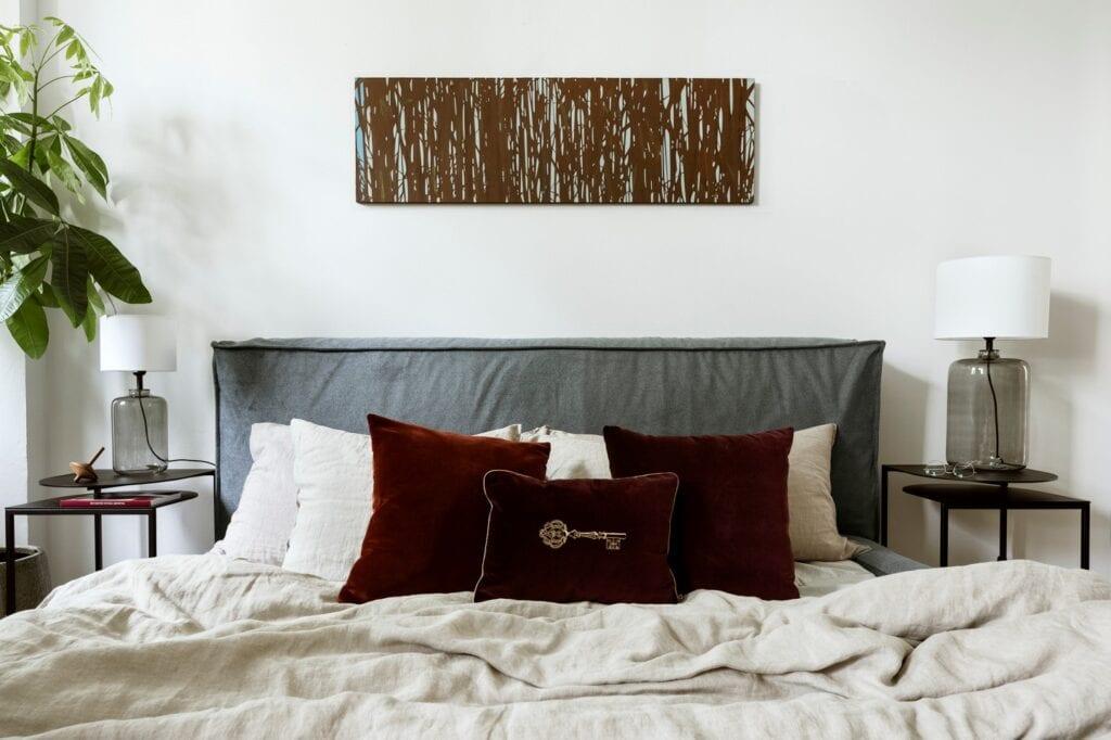 Łóżko tapicerowane NOi C++ (Absynth), pościel lniana (Łyko), poduszka dekoracyjna z kluczem, Limited Edition oraz bordowe poduszki Individuals (Maja Laptos Studio), szklane lampy Ystad (4Concepts), stoliki GAP (Take Me Home), drewniany bączek (Tre Product), sztuka (Galeria Art In Architecture).