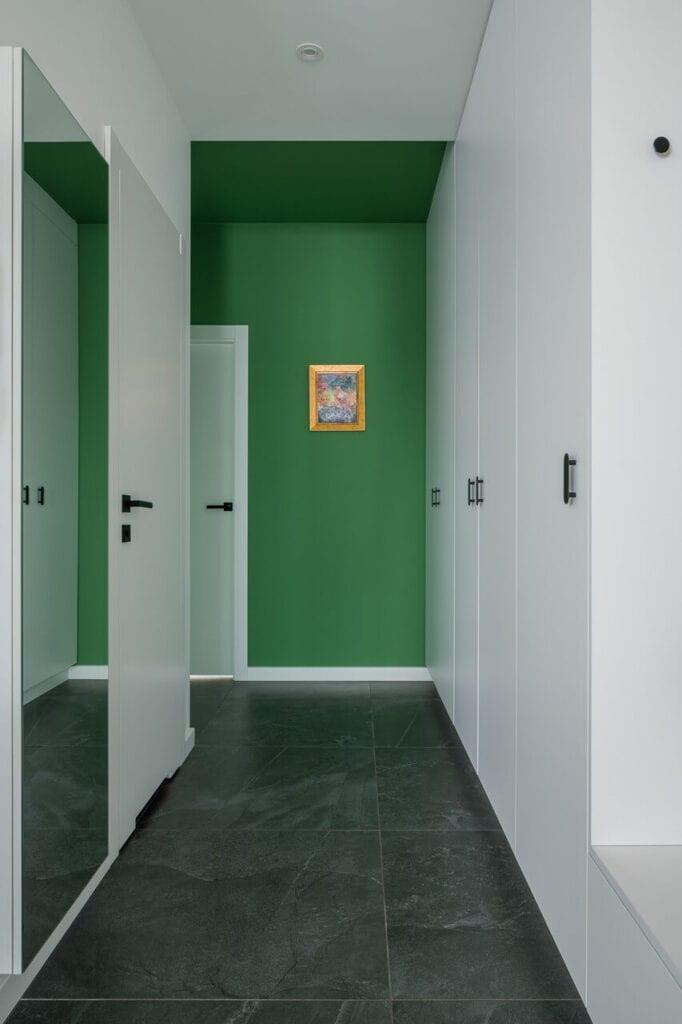 Zielona ściana w przedpokoju - wnętrze 70-metrowego mieszkania dla młodej pary na Starym Polesiu w Łodzi