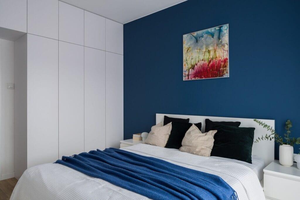 Niebieska ściana w sypialni - wnętrze 70-metrowego mieszkania dla młodej pary na Starym Polesiu w Łodzi