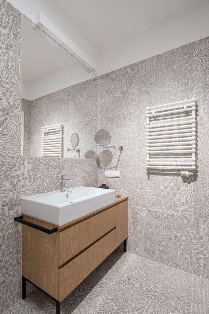 Biały grzejnik łazienkowy w szarej łazience - wnętrze 70-metrowego mieszkania dla młodej pary na Starym Polesiu w Łodzi