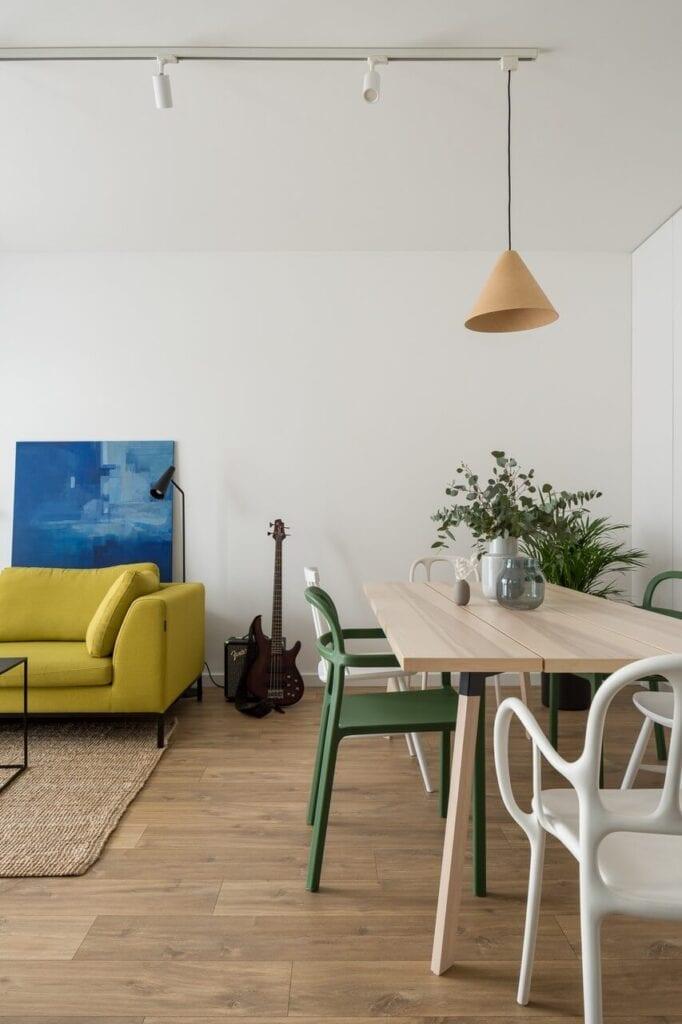 Jasny salon z drewnianym stołem - wnętrze 70-metrowego mieszkania dla młodej pary na Starym Polesiu w Łodzi