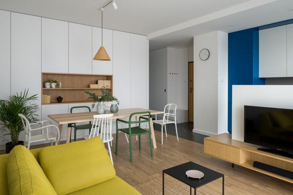 Biała zabudowa w salonie - wnętrze 70-metrowego mieszkania dla młodej pary na Starym Polesiu w Łodzi