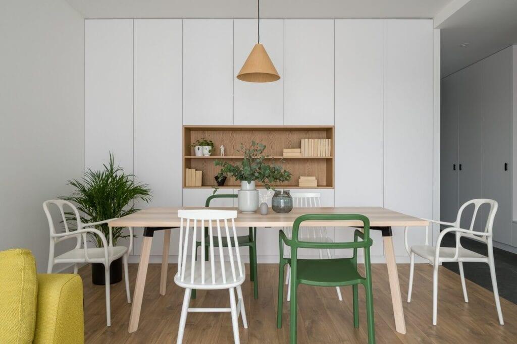 Jasny salon z drewnianym stołem i krzesłami - wnętrze 70-metrowego mieszkania dla młodej pary na Starym Polesiu w Łodzi