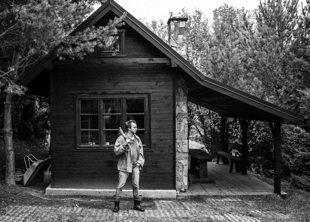 Artysta na tle ukończonego domku fot. Bartosz Mucha
