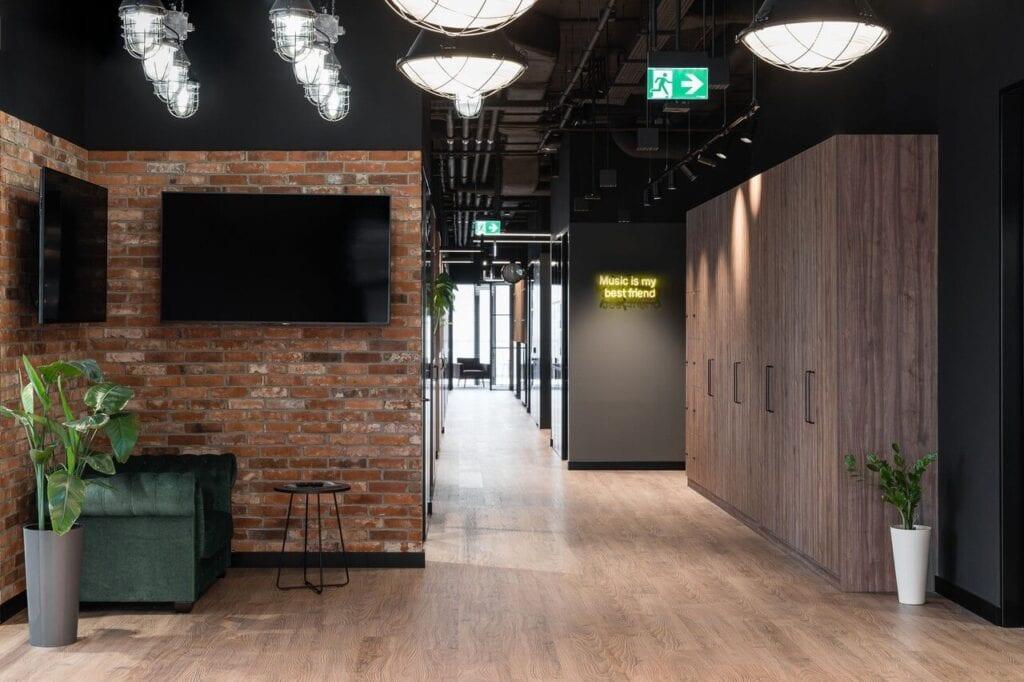 Korytarz z ceglaną ścianą - Wnętrze nowego biura Universal Music Polska w Warszawie projektu The Design Group