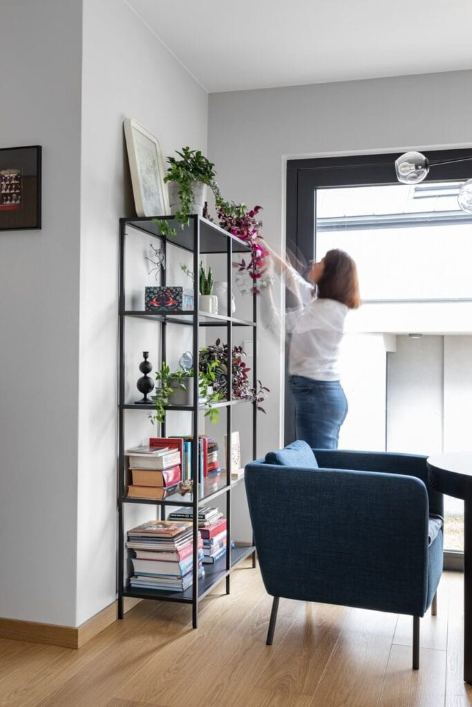 Regał z roślinami i książkami w pokoju - foto INKADR Fotografia wnętrz Natalia Kaczmarek