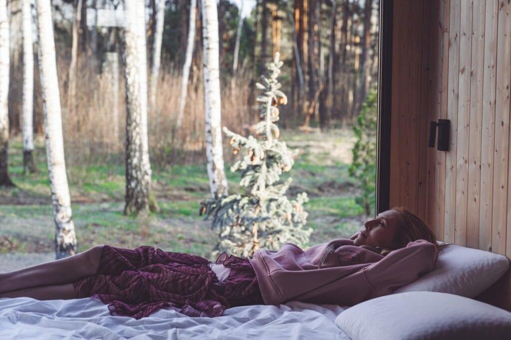 Kobieta leżąca na łóżku w domku letniskowym