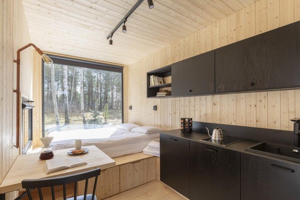 Sypialnia połączona z kuchnią w domku letniskowym Tiny House