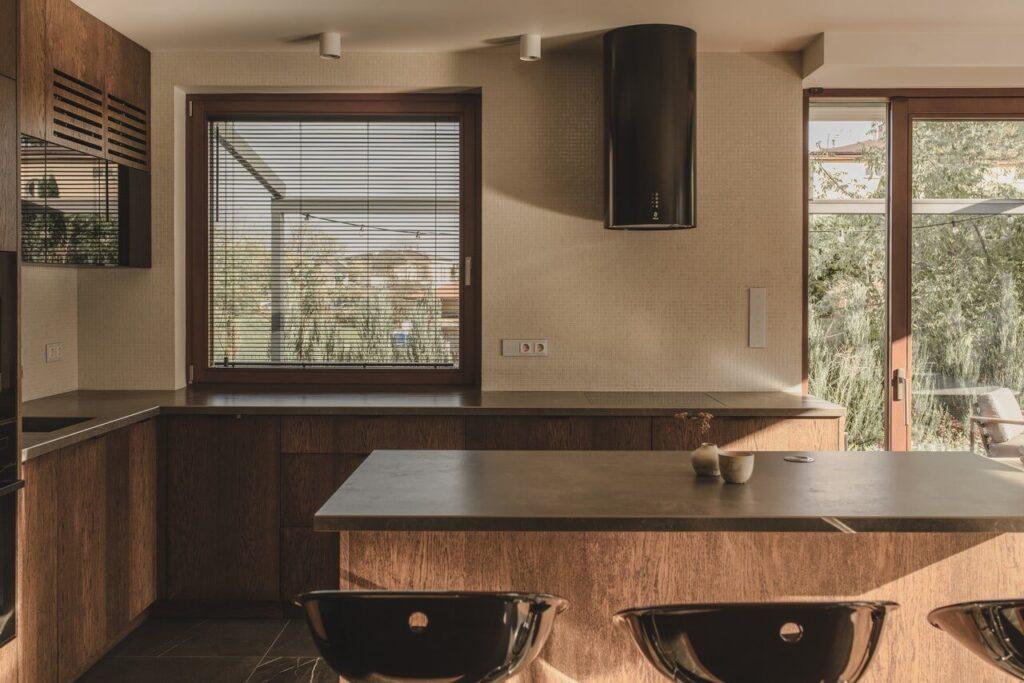 110-metrowe spersonalizowane mieszkanie od pracowni Projektyw - czarny okap w kuchni z wyspą