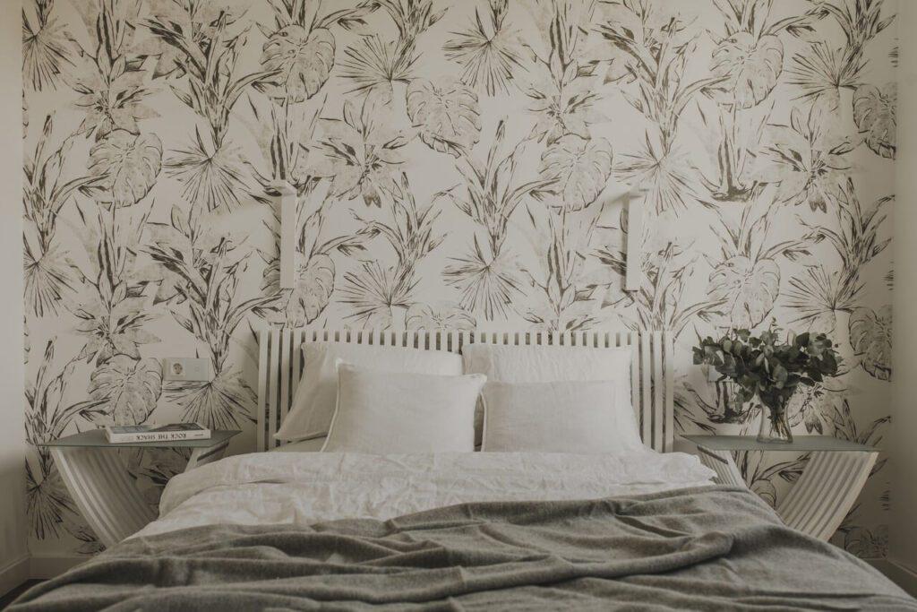 Spersonalizowany projekt mieszkania od pracowni Projektyw - tapeta z motywem kwiatowym w sypialni na ścianie za łóżkiem