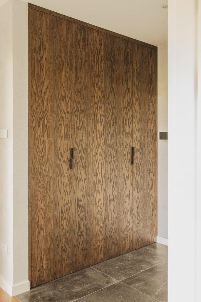 Spersonalizowany projekt mieszkania od pracowni Projektyw - drewniane drzwi w holu