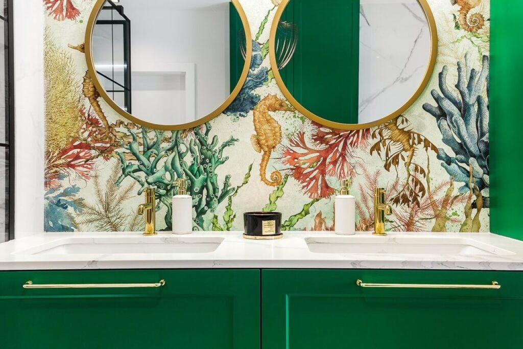 Kolorowa tapeta, dwa okrągłe lustra w złotej ramie oraz meble z frontami w kolorze butelkowej zieleni