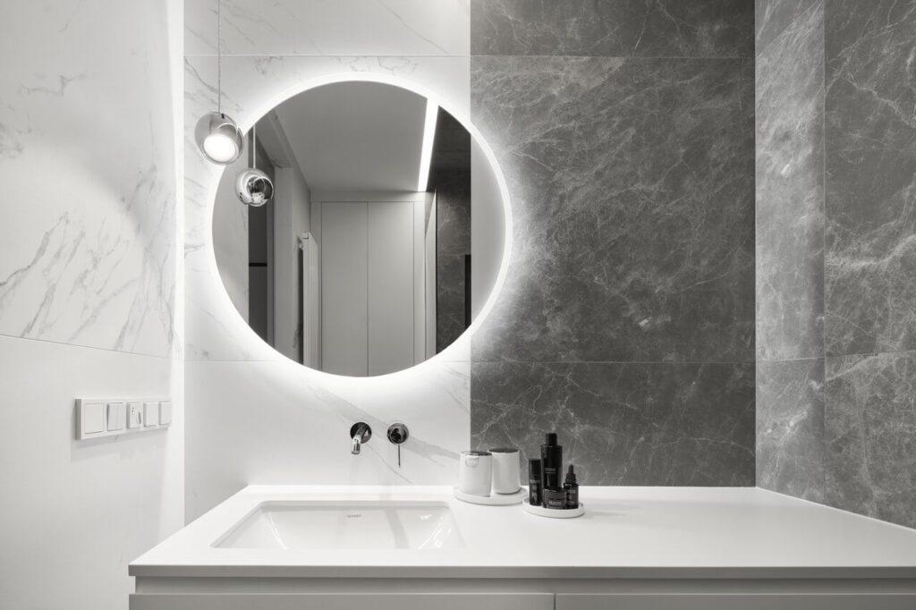 Duże, okrągłe lustro w łazience nad umywalką
