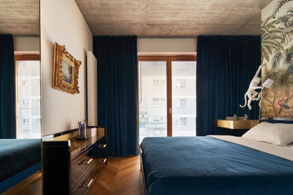 53-metrowy apartament dla młodego małżeństwa - duże łóżko w spyialni z granatowymi zasłonami