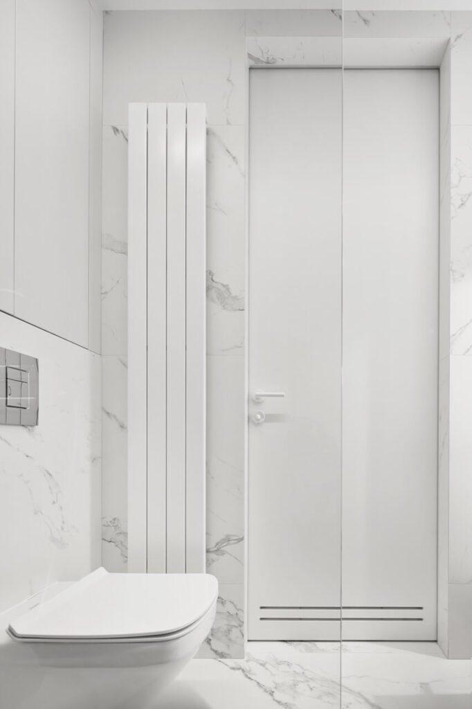 Biały, pionowy grzejnik w jasnej łazience