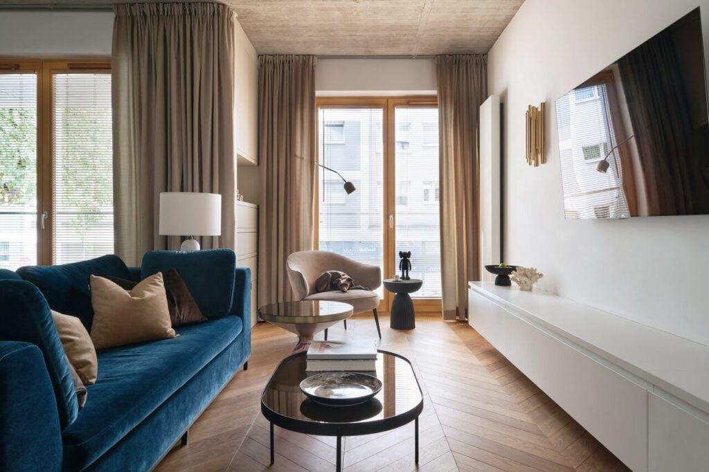 53-metrowy apartament dla młodego małżeństwa - stylowy pokój z granatową kanapą i drewnianą podłogą