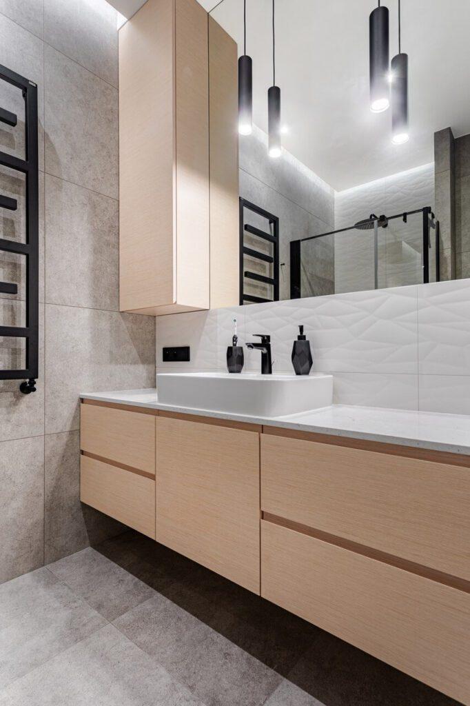 Czarny grzejnik w jasnej łazience - 71-metrowe mieszkanie na Woli projektu Modify
