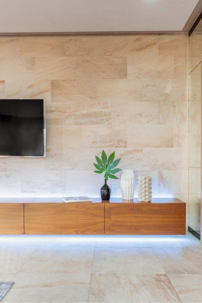 Telewizor na ścianie w beżowym kolorze w projekcie Agnieszki Morawiec z Grupa Siedem