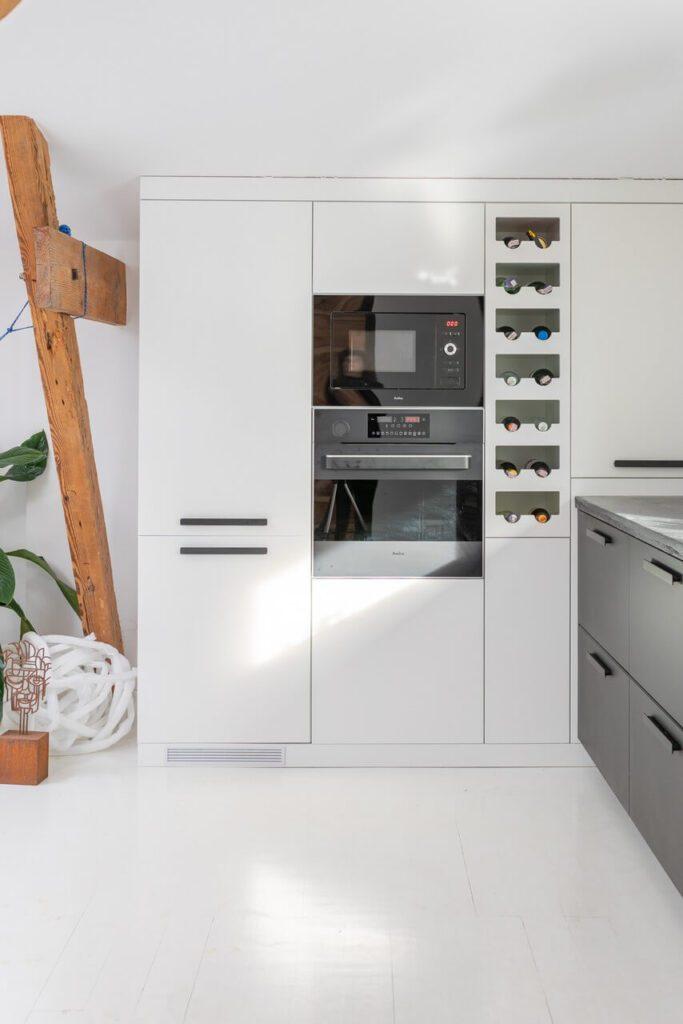 Biała zabudowa kuchenna w mieszkaniu na poddaszu projektu Szalbierz Design - foto Maja Musznicka Shine Studio