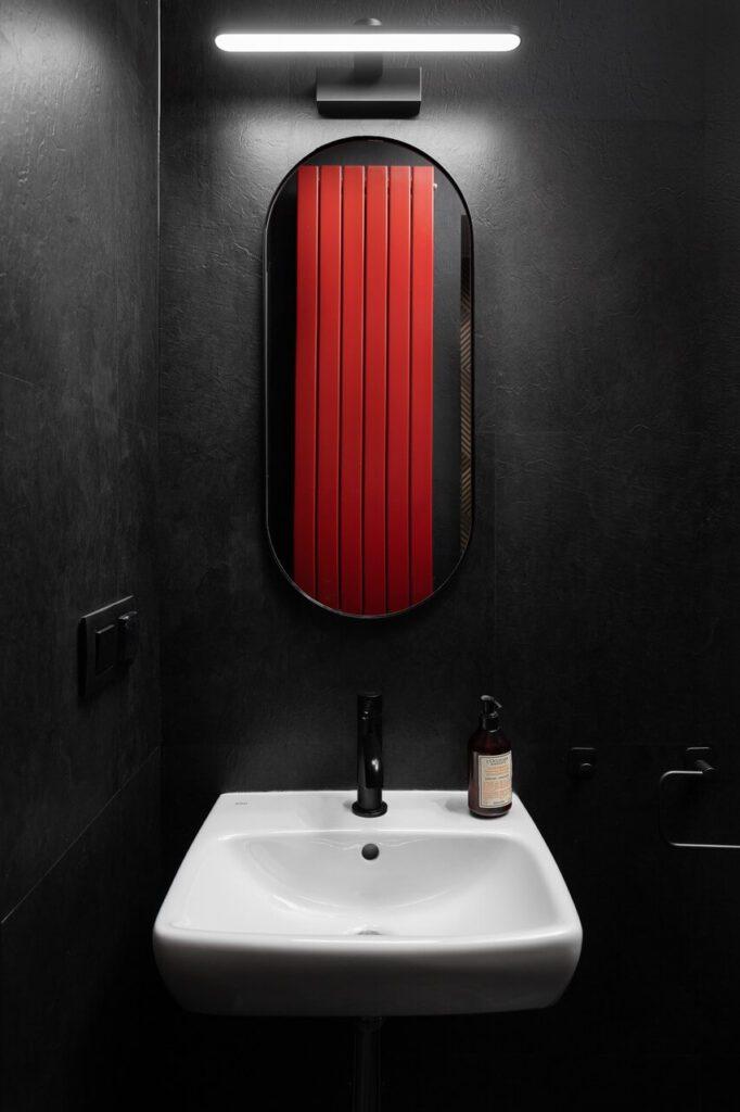 Czarna łazienka z czerwonym grzejnikiem