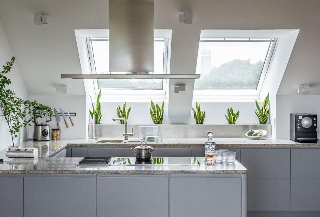 Szara wyspa kuchenna w kuchni ze skosami
