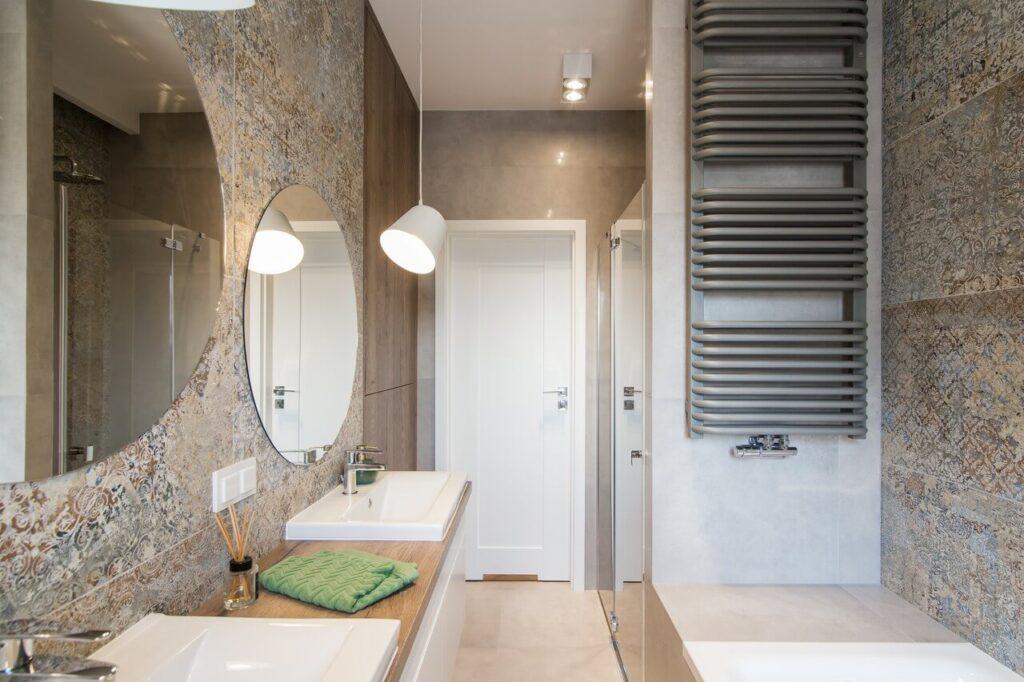 Jasna łazienka z okrągłym lustrem i ciemnym grzjenikiem