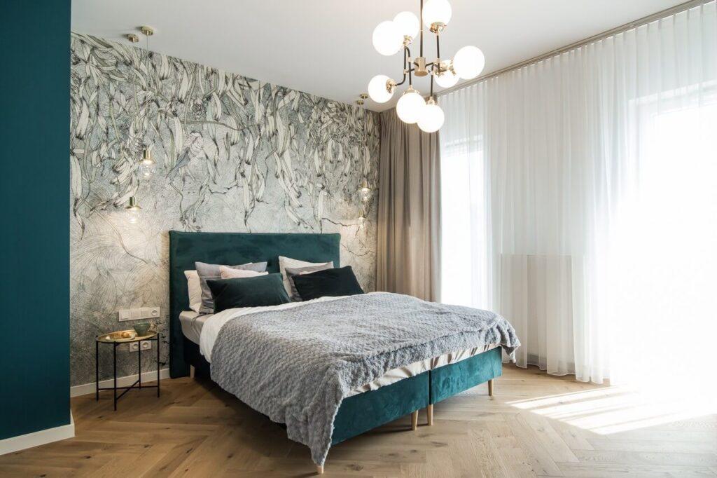 Duże łóżko w kolorze turkusowym w sypialni