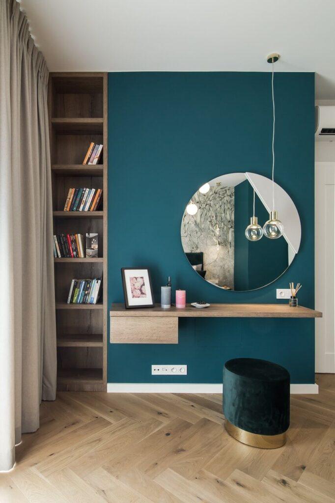 Turkusowa ściana w sypialni a na niej okrągłe lustro